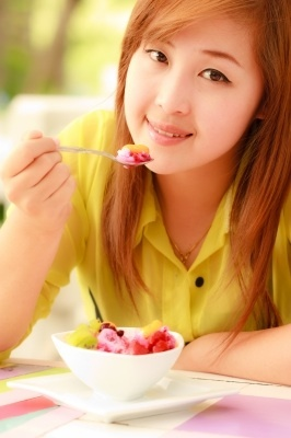 Asian girl eating fruit
